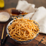 A bowl of messy hibachi noodles topped with sesame seeds and chopsticks on the table.