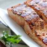 Two honey garlic salmon fillets on a white plate.