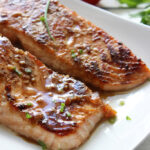 A close up shot of two honey garlic salmon fillets on a white plate.