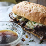 A hearty slow cooker French dip sandwich on white parchment paper with a bowl of au jus dip.