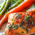 Slow cooker honey garlic chicken thighs on a white plate with carrots and green beans.