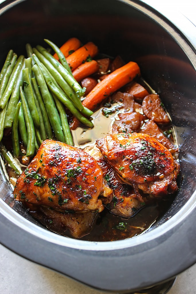 Top down shot of honey garlic chicken with potatoes, green beans and carrots in a slow cooker.