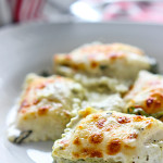 Spinach and artichoke ravioli bake in a white plate.