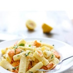 A plate of salmon pasta with fresh basil and lemon wedges.
