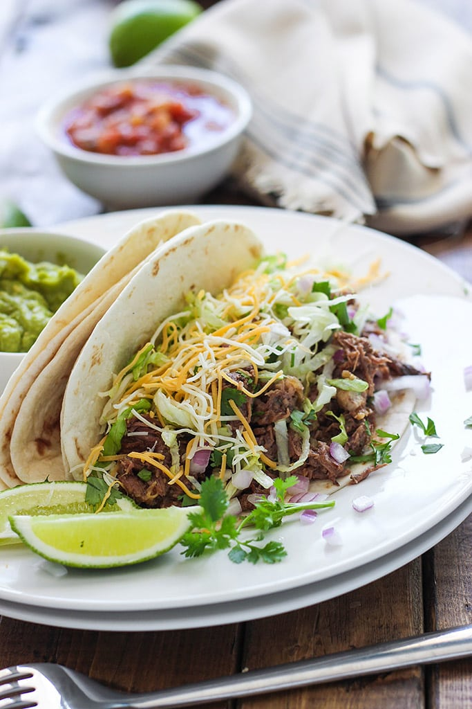 These slow cooker shredded beef tacos are summer slow cooking at its best! Pair it with your favorite toppings.