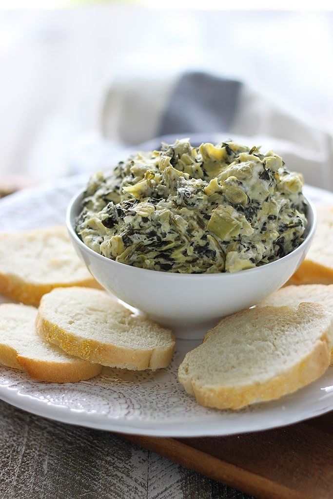 Slow cooker spinach and artichoke dip on a white plate surrounded by sliced French bread.