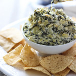 Slow cooker spinach and artichoke dip on a white plate surrounded by chips.