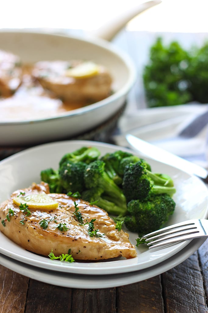 A chicken breast with lemon garlic cream sauce on a white plate with a side of fresh broccoli.
