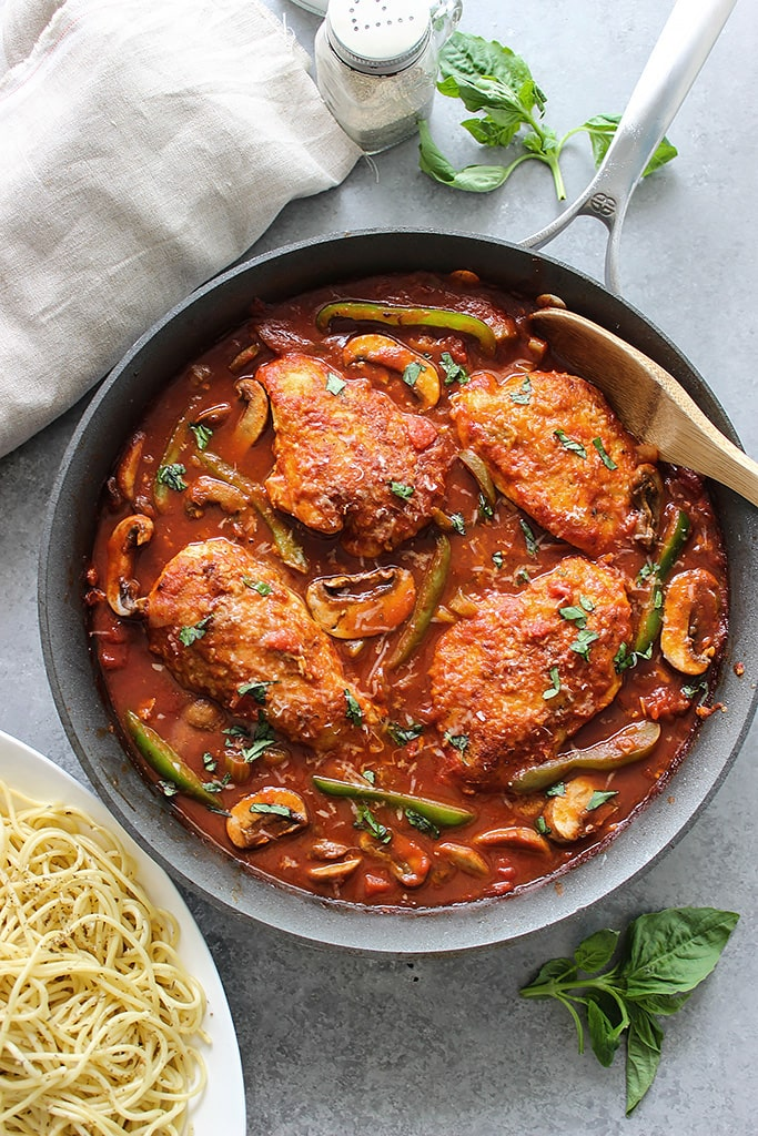 Skillet chicken cacciatore stewed in a robust red sauce with fresh peppers, mushrooms and basil is a hearty meal for 4. Serve over pasta with Parmesan cheese.