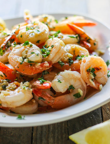 Shrimp scampi on a plate of pasta.