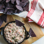 Cream cheese sausage dip in a cast iron bowl with some purple tortilla chips.