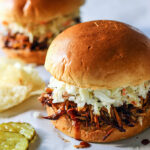 Two slow cooker BBQ pulled chicken burgers topped with coleslaw with pickles and chips.
