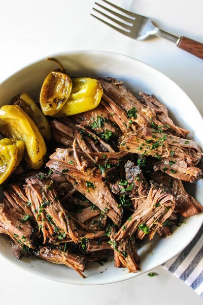 Shredded Mississippi pot roast in a bowl with pepperoncini peppers.
