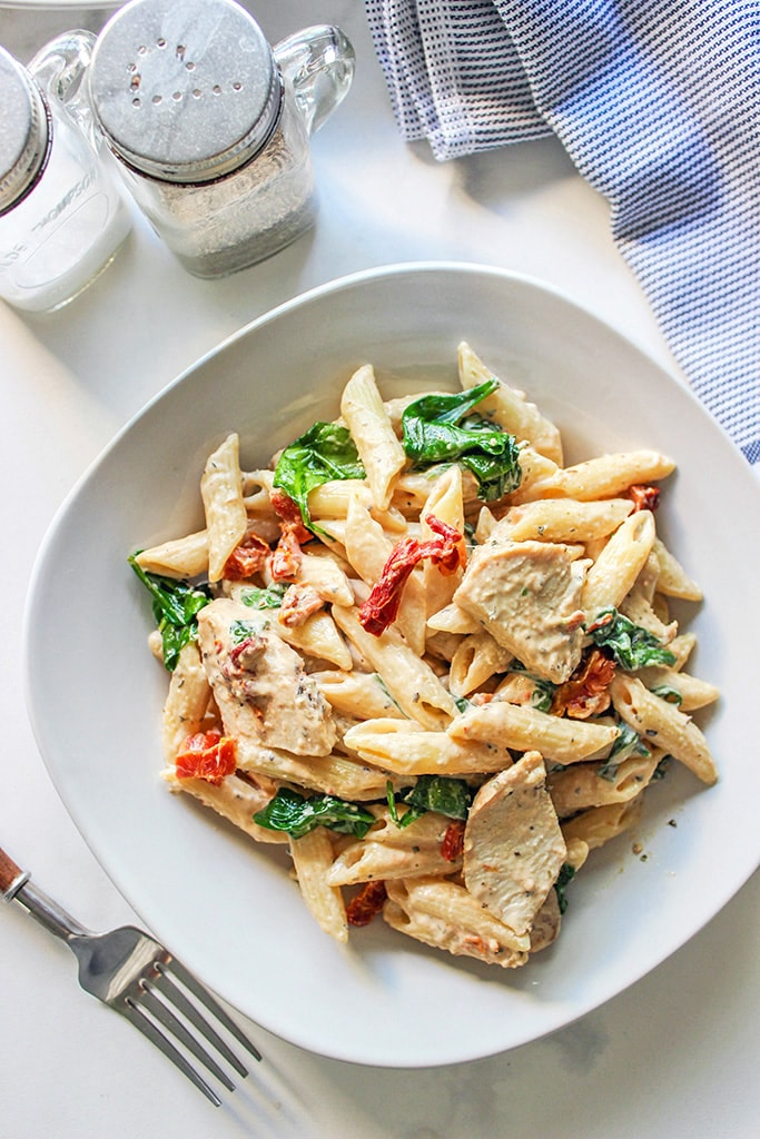 Creamy Tuscan chicken pasta served on a white plate.