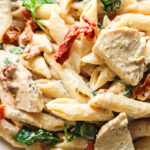 A closeup of sun-dried tomatoes, spinach and chicken in creamy Tuscan chicken pasta.