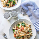 An artistic shot of two plates of creamy Tuscan chicken pasta with utensils, a dish towel and salt and pepper shakers.