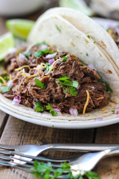 Slow cooker shredded beef tacos on a white plate with cilantro, red onions and cheese toppings.