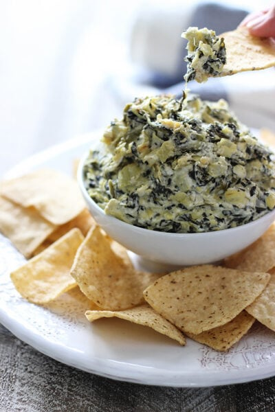 Slow cooker spinach and artichoke dip in a white bowl surrounded by chips.