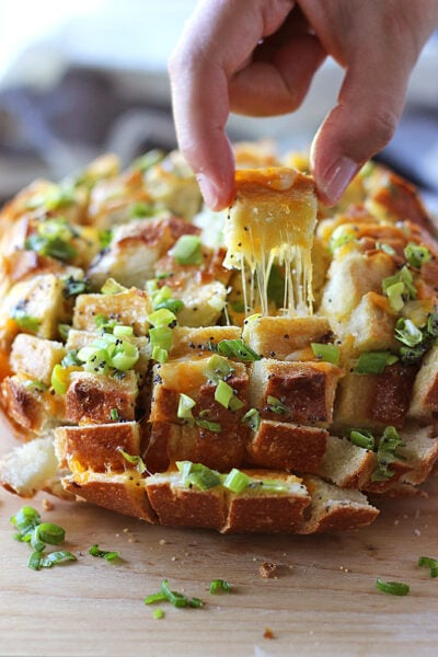 A piece of bloomin' onion pull-apart bread being pulled out with cheese strings.