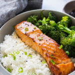 A bowl of honey garlic salmon with rice and broccoli.