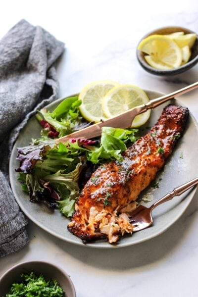 A flaked air fryer honey mustard salmon fillet on a plate with a leafy salad and two lemon slices.