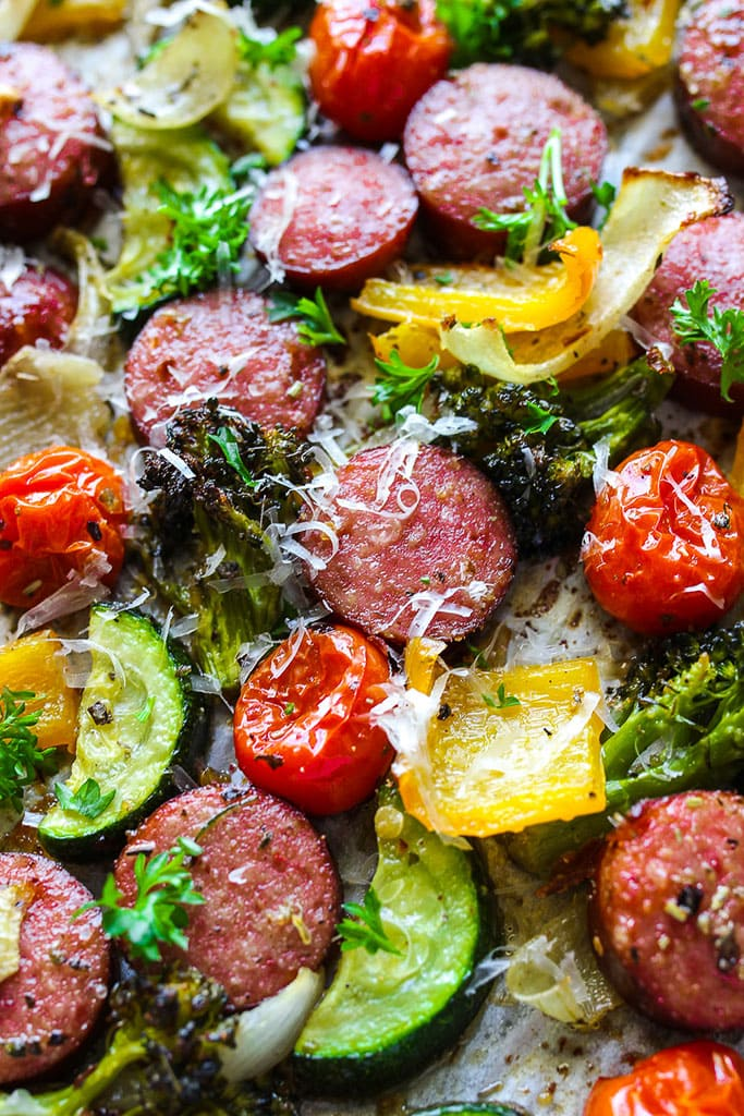 A close up picture of sausage and veggies with parsley and parmesan cheese.