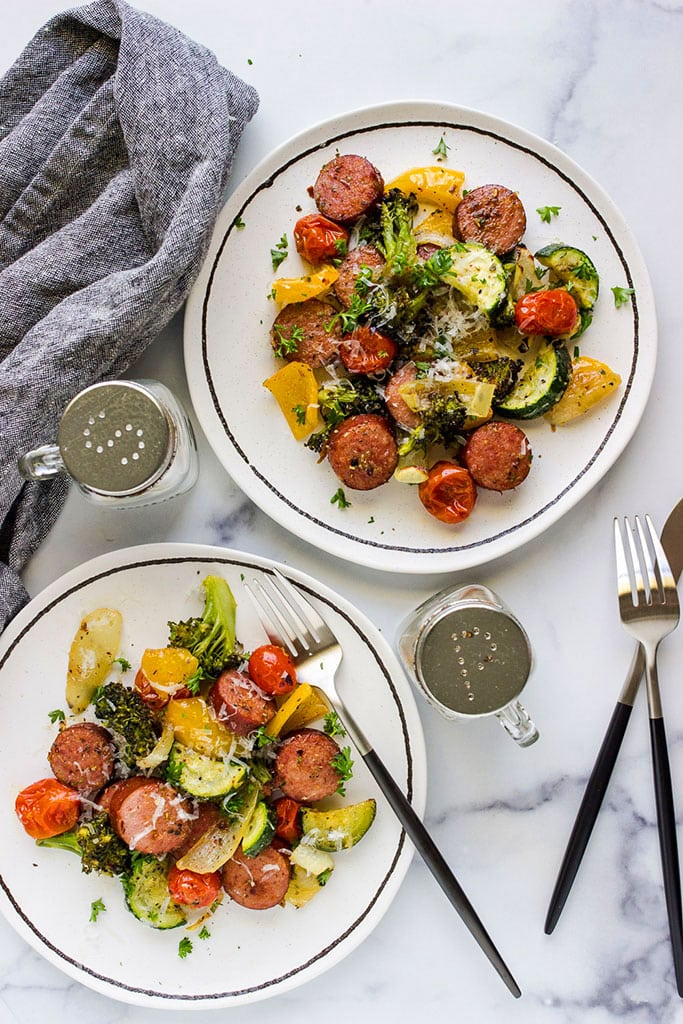 Healthy sheet pan sausage and veggies on two white plates.