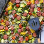 A sheet pan of sausage and veggies with parsley and parmesan cheese.