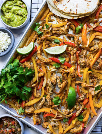 Some chicken fajitas in a sheet pan with onions, bell peppers, cilantro and lime wedges.