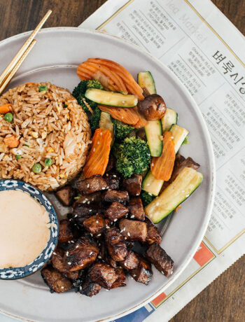 Hibachi rice, veggies and steak on a white plate with a side of Yum Yum sauce.