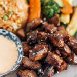 A close up shot of hibachi steak on a plate with hibachi rice, veggies and Yum Yum sauce in the background.
