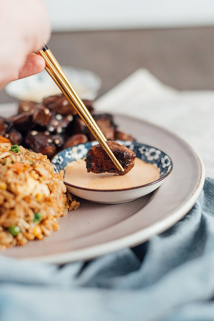 A pair of gold and black chopsticks holding a piece of hibachi steak while dipping into a bowl of Yum Yum sauce.