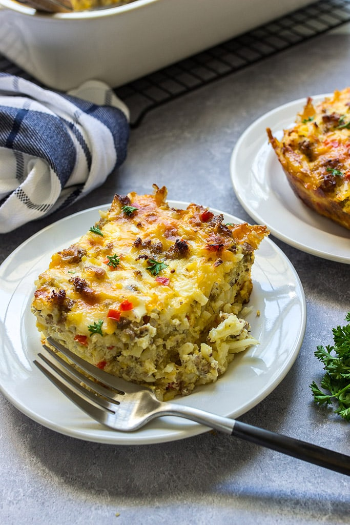 Two slices of hash brown breakfast casserole on white plates.