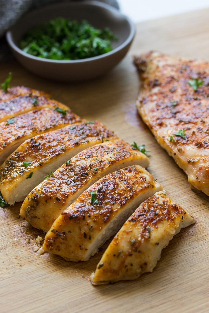 Sliced oven-baked chicken breasts on a cutting board.