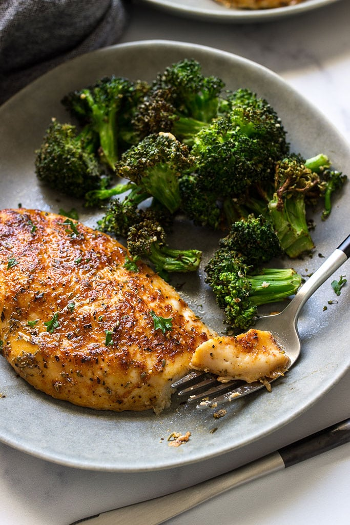 An oven-baked chicken breast on a gray plate with a side of crispy broccoli.