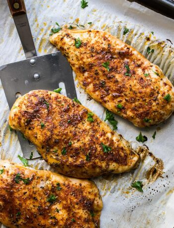 Three freshly baked chicken breasts on parchment paper on a baking sheet.