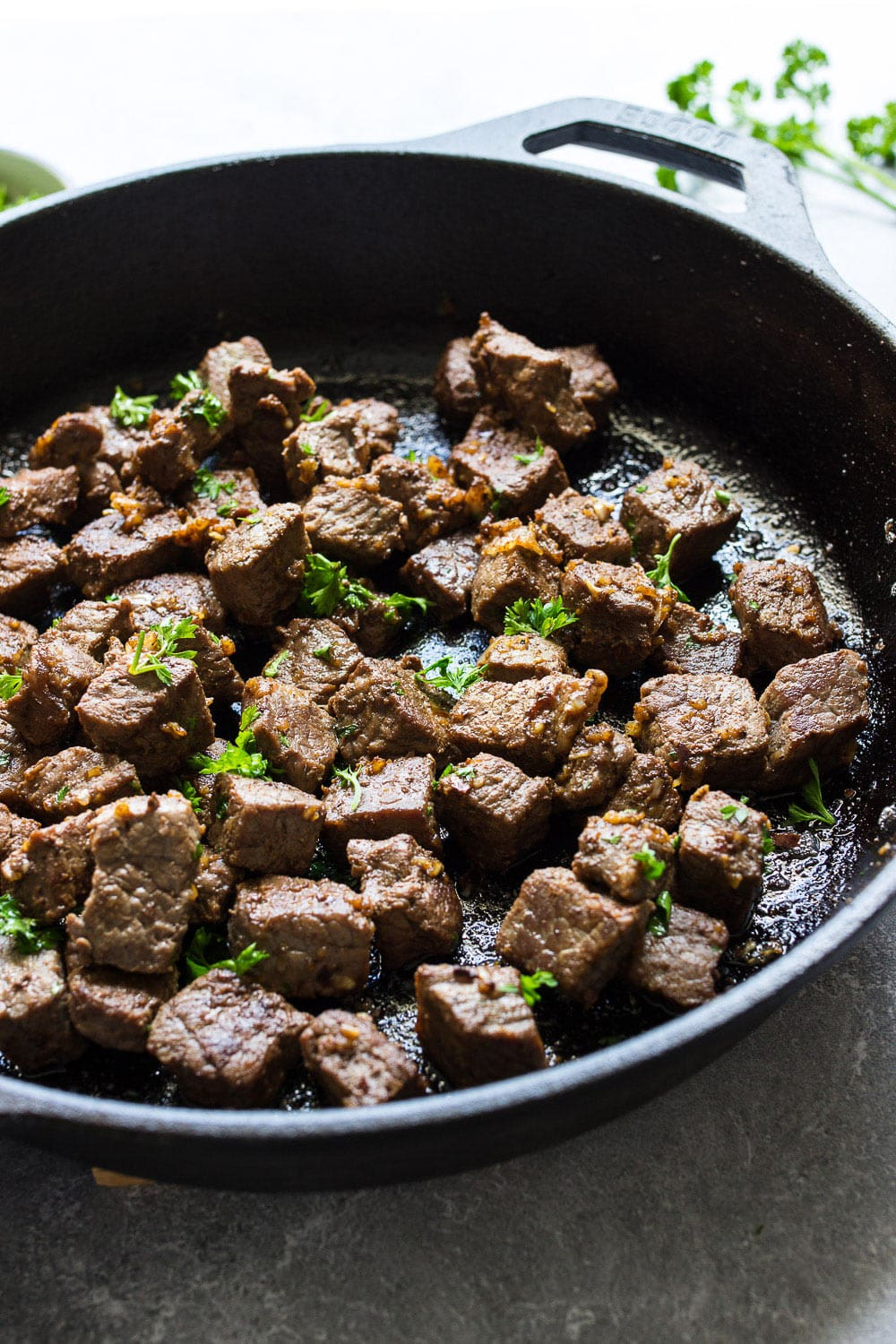 Some garlic butter steak bites in a cast iron pan topped with fresh parsley.