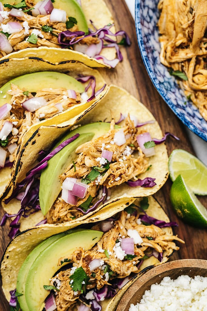 Several chipotle chicken tacos on charred corn tortillas with purple cabbage, avocado, red onions, cilantro and limes.