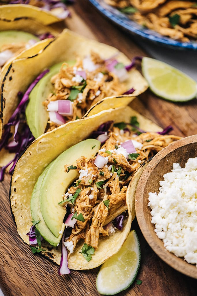 Several chipotle chicken tacos on charred corn tortillas with purple cabbage, avocado, red onions, cilantro, queso fresco and limes.