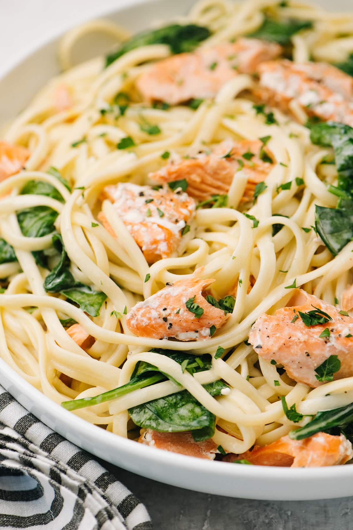 A close up shot of creamy salmon pasta with spinach on a white plate.