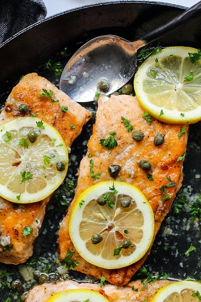 Salmon piccata in a cast iron pan topped with capers, lemon slices and fresh parsley.