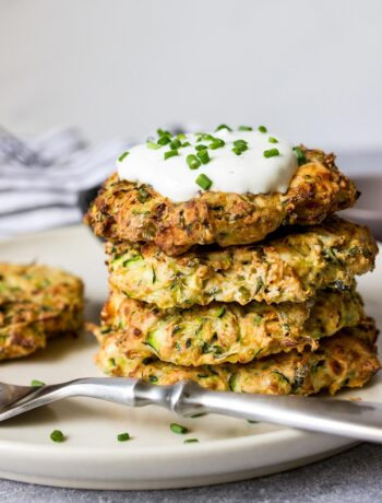Some air fryer zucchini fritters on a white plate with a yogurt dip and fresh chives.