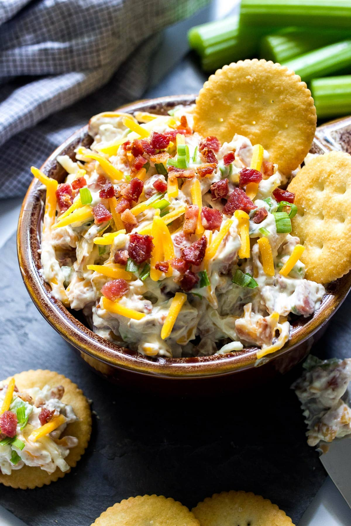 Million dollar dip in a brown bowl with some crackers and topped with shredded cheddar cheese, bacon bits and green onions.