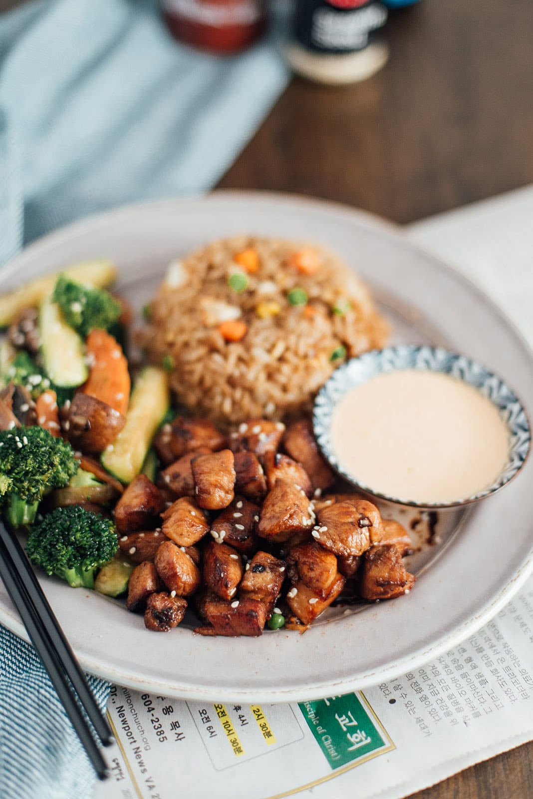 Hibachi rice, chicken and veggies on a white plate with some yum yum sauce on the side.