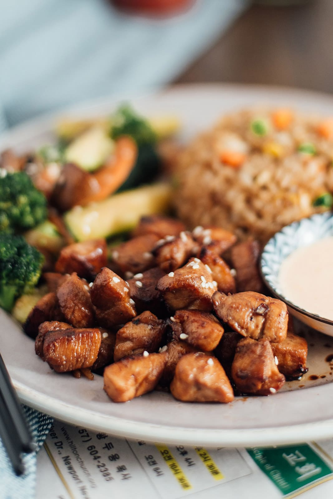 A close up shot of hibachi chicken with hibachi rice and vegetables in the background.