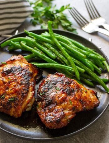 A black plate full of crispy air fryer maple chicken thighs with some green beans.