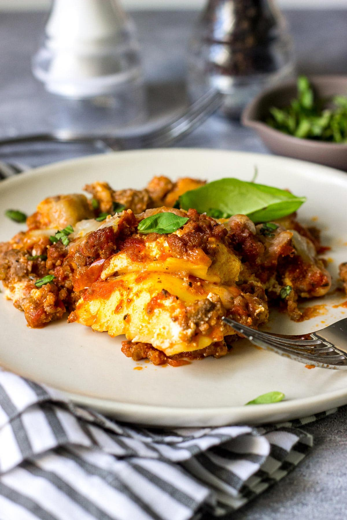 A hearty serving of ravioli lasagna on a plate topped with fresh basil.
