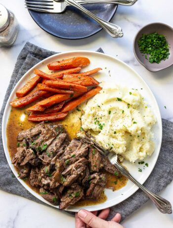 A plate of shredded chuck roast with mashed potatoes and carrots topped with fresh parsley.