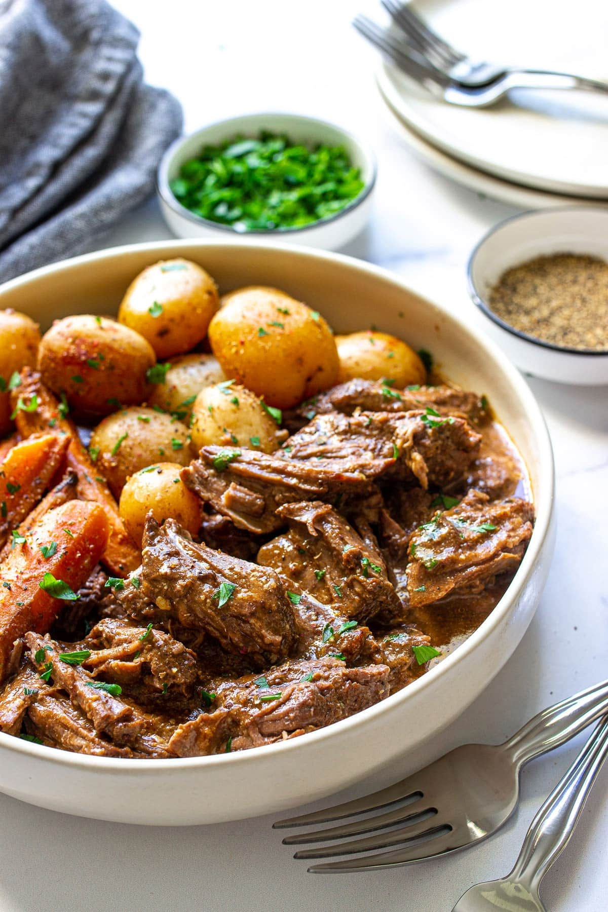 A big bowl of slow cooker pot roast with tender beef, baby yellow potatoes and carrots topped with fresh parsley.